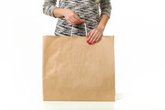 Girl with shopping bags on a white background. Female hand holding shopping bags. Hand of a woman holding many white shopping bags. Isolated on white Royalty Free Stock Image