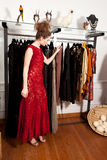 Girl shopping in boutique. Girl in a red dress shopping in a boutique clothing shop in front of hanging fashion dresses Royalty Free Stock Photography