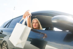 Girl with shopping in car. Photo of girl with shopping in car on summer day Royalty Free Stock Photo