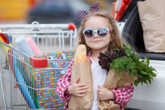 Girl with a shopping cart full of groceries near the car Royalty Free Stock Photography