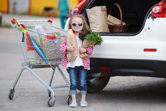 Girl with a shopping cart full of groceries near the car Royalty Free Stock Photo