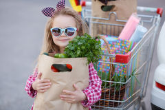 Girl with a shopping cart full of groceries near the car Royalty Free Stock Image