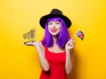 Girl with shopping cart and Great Britain flag. Portrait of young style hipster girl with purple hairstyle with shopping cart and Great Britain flag in hand on Stock Image