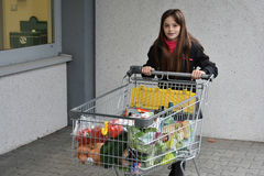 Girl with shopping cart. Teenage girl with shopping cart, she bought grocery in a supermarket Stock Photo