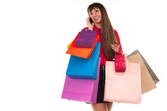 Girl shopping with credit card, paper bags, talking on phone Royalty Free Stock Photography