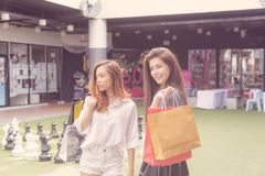 Girl shopping in department store. Asia girl and friend ethnic German-Thai go shopping holding bag and smart phone in a department store. tone retro color Stock Photo