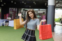 Girl shopping in department store. Girl half blood ethnic German-Thai go shopping with happy and smile on face and holding paper bag in a department store Royalty Free Stock Photography