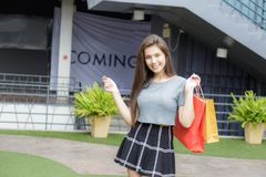 Girl shopping in department store. Girl half blood ethnic German-Thai go shopping with happy and smile on face and holding paper bag in a department store Royalty Free Stock Photo