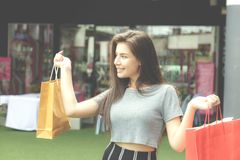 Girl shopping in department store. Girl half blood ethnic German-Thai go shopping with happy and smile on face and holding paper bag in a department store. Tone Royalty Free Stock Photography