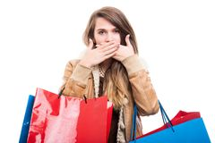 Girl at shopping doing speak no evil gesture. And carrying colorful bags Stock Images