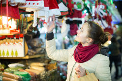 Girl shopping at festive fair before Xmas in evening time Royalty Free Stock Image