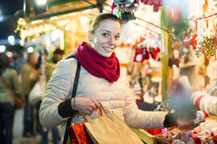 Girl shopping at festive fair before Xmas in evening time Stock Photo