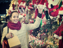 Girl shopping at festive fair before Xmas in evening time Royalty Free Stock Photos