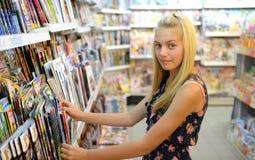 Girl shopping for magazine Stock Images