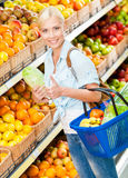 Girl at the shopping mall choosing vegetables Royalty Free Stock Photography
