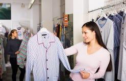Girl shopping sleepwear for man Stock Images