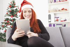 Girl is shopping something for christmas on the tablet Stock Photography