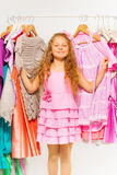 Girl during shopping standing between hangers Royalty Free Stock Image