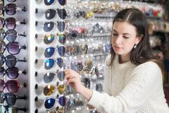 Girl shopping sunglasses in shop market. Young attractive caucasian girl trying on affordable sunglasses. Shopping and consumerism concept Stock Photos