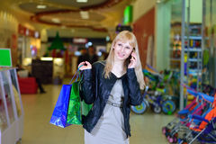 Girl shopping and talking on the phone Stock Images
