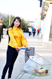 Girl  with shopping trolley. Going from shop to car Royalty Free Stock Photo
