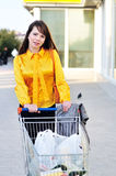 Girl with shopping trolley. Going from shop to car Stock Photography