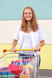 Young buyer. Girl  with shopping trolley full of purchases in the street royalty free stock photo