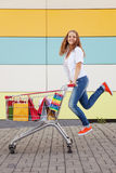 Girl  with shopping trolley Stock Photos