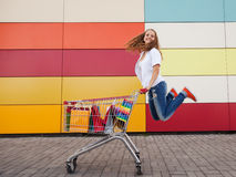 Girl  with shopping trolley Stock Images