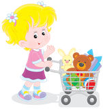 Girl with a shopping trolley of toys. Little buyer going with a supermarket trolley filled with toys Stock Photography