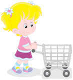 Girl with a shopping trolley of toys. Little buyer going with a supermarket trolley filled with toys Royalty Free Stock Photography