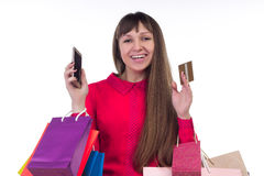 Girl shops with credit card holding colourful paper bags, smartp Stock Photography