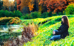 Girl on a Shore. Beautiful girl sitting on a shore in autumn forest Stock Images
