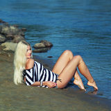 The girl on the shore. Fashionable beautiful blonde in a striped blouse enjoying on the beach Stock Photography