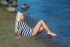 The girl on the shore. Fashionable beautiful blonde in a striped blouse enjoying on the beach Stock Images