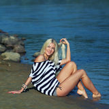 The girl on the shore. Fashionable beautiful blonde in a striped blouse enjoying on the beach Royalty Free Stock Photo
