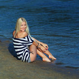 The girl on the shore. Fashionable beautiful blonde in a striped blouse enjoying on the beach Royalty Free Stock Photos