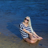 The girl on the shore. Fashionable beautiful blonde in a striped blouse enjoying on the beach Stock Image