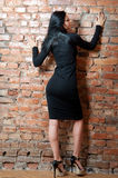 Girl in short black dress. Brick wall Royalty Free Stock Image