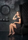 Girl in a short black dress sitting in a high chair Royalty Free Stock Images