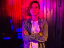 A girl with short blonde hair stands in a rock club in the rays of red and blue light stock images
