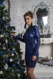 Girl in short blue dress near christmas decorated commode Stock Images