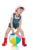Girl in a short denim overalls, hat and rubber Royalty Free Stock Photo