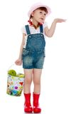Girl in a short denim overalls holding Royalty Free Stock Image