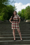 Girl in short  dress. A woman in short  dress standing on a stone staircase Stock Photos