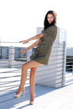 Girl in a Short Dress Hanging on a Fence Royalty Free Stock Photos