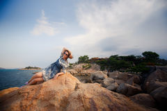Girl in short grey frock lies on rock against stones plants Royalty Free Stock Images