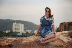Girl in short grey frock sits on rock shows legs against city Stock Photos