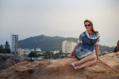 girl in short grey frock sits on rock shows legs against city Royalty Free Stock Photography