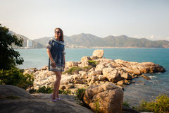 Girl in short grey frock stands on rocks by sea against city Royalty Free Stock Image